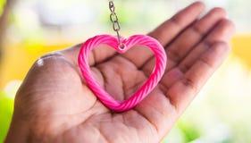 rosa hjärta på handen för valentin & x27; s-dag man för begreppskyssförälskelse till kvinnan Royaltyfria Bilder