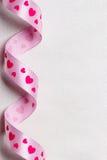Rosa hjärtaband på torkdukebakgrund Arkivbild