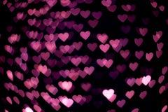 Rosa hjärtabokeh i mörkret Arkivbild