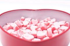 Rosa hjärtagodisar i hjärtaformasken för valentindagisolat royaltyfria foton