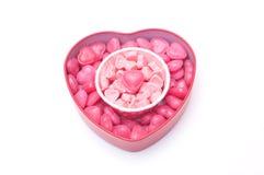 Rosa hjärtagodisar i kopp och i hjärtaform boxas för valentin D royaltyfri bild