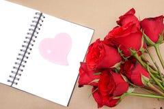 Rosa hjärtapapper på den öppna anteckningsboken med röda rosor Royaltyfri Fotografi