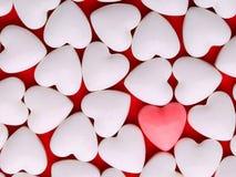 Rosa hjärta mellan en hög av vita hjärtor godisen har hjärtor mig en smstext dem Arkivbilder