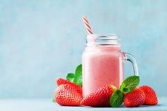 Rosa jordgubbesmoothie eller milkshake i murarekrus på blåtttabellen Sund mat för frukost och mellanmål arkivbild