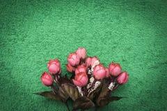 Rosa künstliche Blumen auf einem Grünsmaragdhintergrund Lizenzfreie Stockbilder