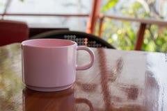 Rosa Kaffeetasse gesetzt auf ein Holztischfunkeln Lizenzfreies Stockbild