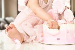 Rosa kaka för krasch på berömmen av den första födelsedagen av flickan, förstörd sockerkaka, bruten marshmallow, 1 år arkivfoto