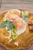 rosa kaka som dekoreras med ranunculusblommor på ett guld- magasin arkivfoto