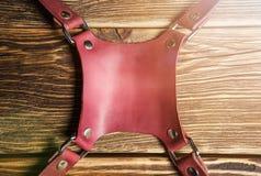Rosa kamerasele för central del, mång--kamera remsele, läderkamerarem på brun träbakgrund ljus Arkivbild