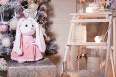 Rosa Kaninchen, das auf einer Geschenkbox unter Weihnachtsbaum steht Stockbild