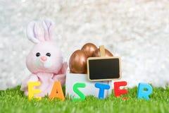 Rosa Kaninchen und rosafarbenes Gold-Osterei im hölzernen weißen Kasten und im freien Raum Lizenzfreie Stockfotos