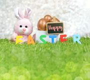 Rosa Kaninchen und rosafarbenes Gold-Osterei im hölzernen weißen Kasten und glücklich Stockfotografie