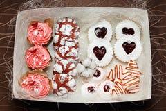 Rosa Kekse mit Erdbeere und kleinen Kuchen in einem Kasten Stockfoto
