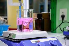 Rosa kemisk vikt i dryckeskärlen som förläggas på den magnetiska blandaren Arkivfoton