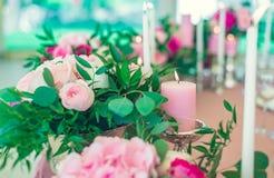 Rosa Kerzen und Blumen auf dem Tisch Stockfoto