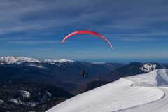 The snowboarders, skiers in action at the mountains.Paraglider with an instructor. royalty free stock photos