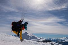 The snowboarders, skiers in action at the mountains.Paraglider with an instructor. stock photo