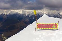 ROSA KHUTOR, RÚSSIA - 31 DE MARÇO DE 2016: Sinal de aviso na opinião superior do cenário de Rosa Peak em montanhas de Cáucaso nev Imagens de Stock Royalty Free