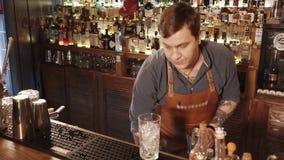 Rosa Khutor, RÚSSIA - em fevereiro de 2018: o barman está estando atrás da cremalheira da barra está misturando cocktail em dois  video estoque