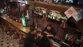 Rosa Khutor, RÚSSIA - em fevereiro de 2018: o homem e a mulher estão falando com o empregado de bar na noite video estoque