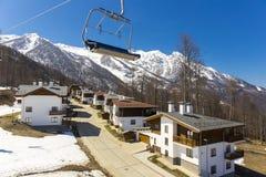 ROSA KHUTOR, RUSIA - 1 DE ABRIL DE 2016: Estación de esquí Rosa Khutor de la montaña y cabañas en fondo nevoso de las montañas Fotografía de archivo