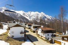ROSA KHUTOR, RUSIA - 1 DE ABRIL DE 2016: Estación de esquí Rosa Khutor de la montaña y cabañas en fondo nevoso de las montañas Fotografía de archivo libre de regalías