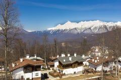 ROSA KHUTOR, RUSIA - 1 DE ABRIL DE 2016: Estación de esquí Rosa Khutor de la montaña y cabañas en fondo nevoso de las montañas Fotos de archivo libres de regalías