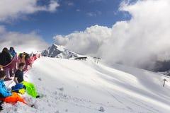 ROSA KHUTOR, RUSLAND - MAART 31, 2016: De toeristen en de ruiters in Rosa Peak zetten hoogste 2320 meters op hoogte stock fotografie