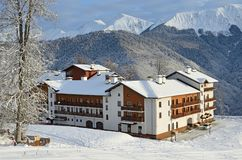 Rosa Khutor, Sochi, Russia, January, 26, 2018. Cottage in the Olympic village on a background of mountain peaks in winter Stock Images