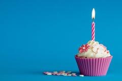 Rosa kleiner Kuchen auf blauem Hintergrund Stockbilder
