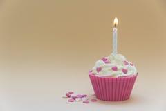 Rosa kleiner Kuchen mit brennender Kerze Stockfoto