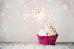 Rosa kleiner Kuchen mit Wunderkerze Lizenzfreie Stockbilder