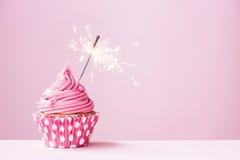 Rosa kleiner Kuchen mit Wunderkerze Stockbilder