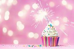Rosa kleiner Kuchen mit Wunderkerze Stockfotografie