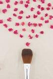 Rosa kronblad för kräppmyrten och sminkborste Arkivfoton