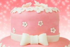 Rosa Kuchen mit Blumen- und Schmetterlingsdekor Stockbild