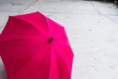 Rosa kulört öppet paraply på jordning arkivbilder