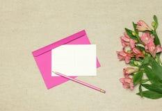Rosa kuvert och tomt papper med blommor på stenbakgrund fotografering för bildbyråer