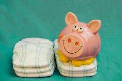 Rosa lächelndes Sparschwein auf grünem Hintergrund stockfotos