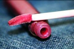 Rosa läppstift på jeansbakgrund Arkivbilder