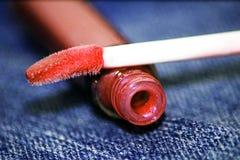 Rosa läppstift på jeansbakgrund Royaltyfri Foto