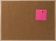 Rosa leeres klebriges Anmerkungsgelb festgesteckt in braunes corkboard Lizenzfreies Stockfoto