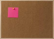 Rosa leeres klebriges Anmerkungsgelb festgesteckt in braunes corkboard Stockfotos