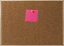 Rosa leeres klebriges Anmerkungsgelb festgesteckt in braunes corkboard Lizenzfreie Stockfotografie