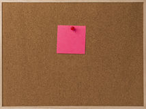 Rosa leeres klebriges Anmerkungsrot festgesteckt in braunes corkboard Stockbilder