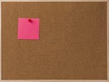 Rosa leeres klebriges Anmerkungsrot festgesteckt in braunes corkboard Lizenzfreie Stockfotografie
