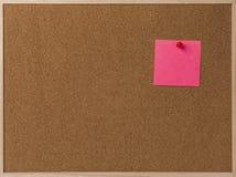 Rosa leeres klebriges Anmerkungsrot festgesteckt in braunes corkboard Stockfotografie