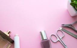 Rosa Lippenstift, Nagellack, rosa Farbe, Parfümflasche, Nagelschere, Nagelfeile, Häutchenquetschwalzen und zierliche Blume in ein stockfotos