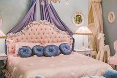 Rosa litet prinsessarum med satäng kudde, sängkantlampor, nattduksbord, ramar på väggarna Lyxig rik sovruminre royaltyfri foto