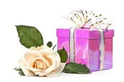 Rosa luminosa e un regalo su una priorità bassa bianca. immagini stock